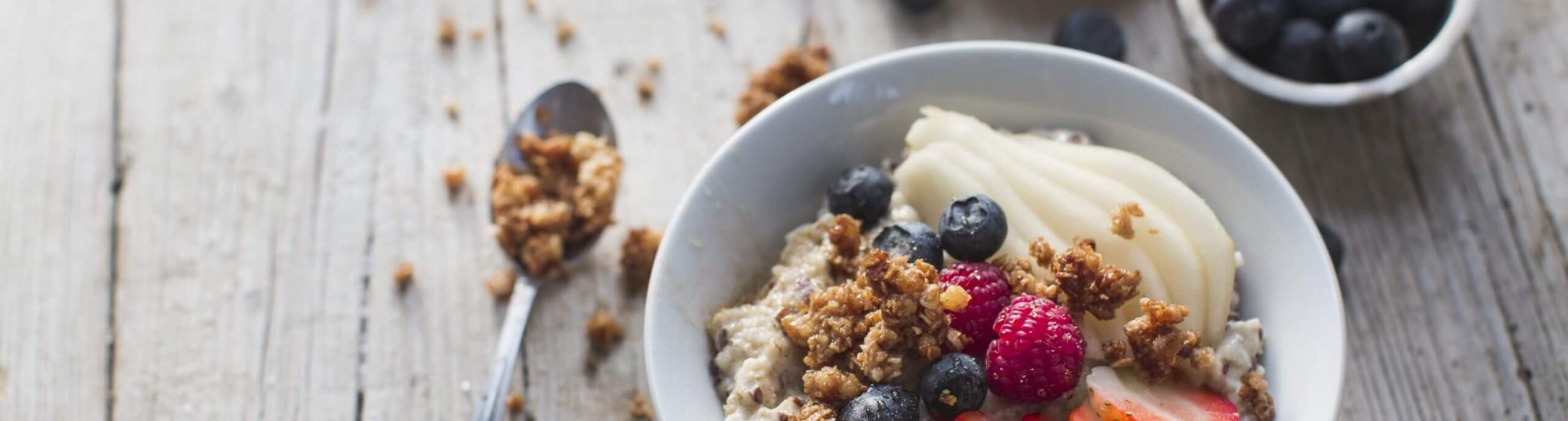 oat cereals porridge with fresh fruits on a wooden table